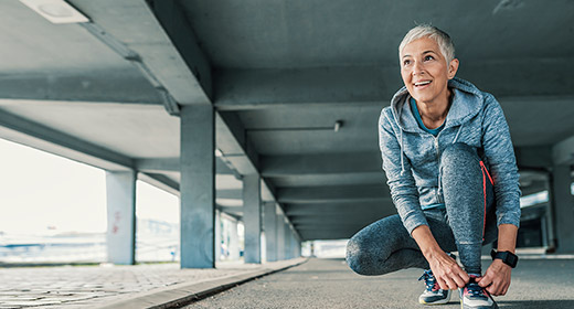 Older woman in running attire stopping to kneel down and tie her shoes