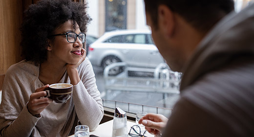 Man and woman sitting in a cafe and enjoying coffee together