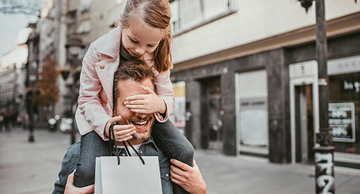 Little girl riding piggyback on her father while holding a shopping bag after leaving a store