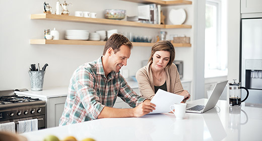 Man and woman sitting at their kitchen island discussing finances and utilizing paper and a laptop