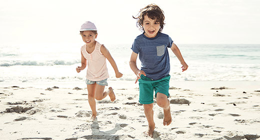 Two kids in shorts and t shirts running on a beach2
