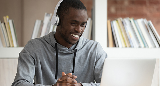 College age man sitting at a table wearing headphones and looking at a laptop