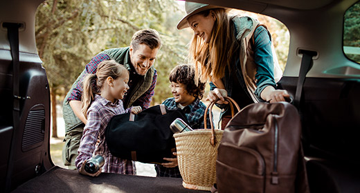 Family of four two kids two parents packing bags into the back of their van for vacation while talking and laughing