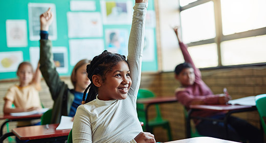 Young child in a classroom raising her hand to answer a question
