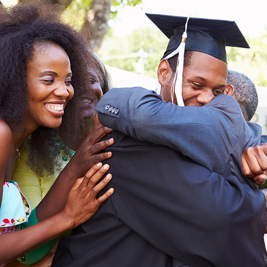 Family congratulating and hugging their son who is in a graduation cap and gown