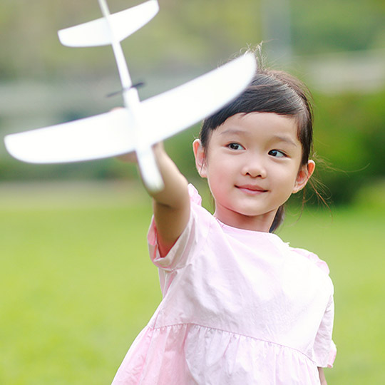 Little girl in a pink dress standing in a grassy park holding out a foam airplane that can be thrown