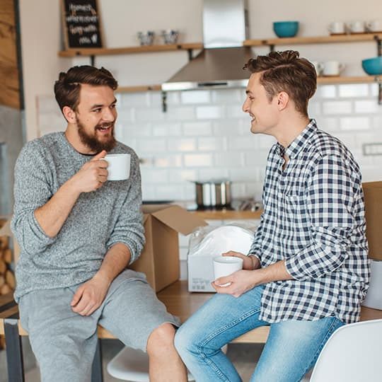 male couple taking a break from unpacking moving boxes at their home by drinking coffee and chatting