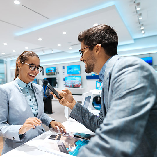 Man in a nice suit holding his phone at a checkout counter to purchase an item