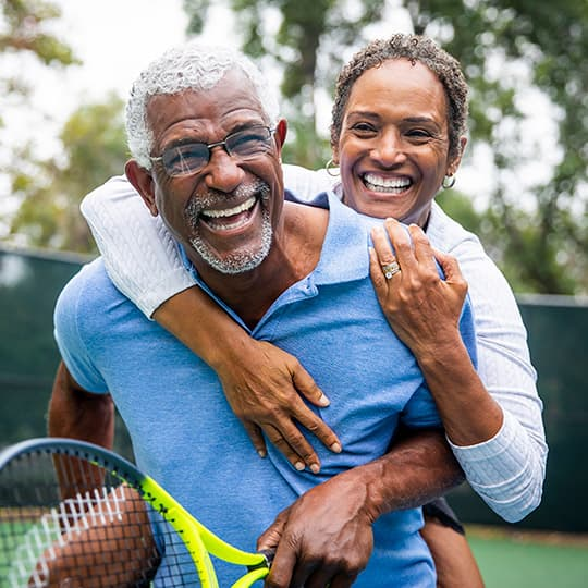 older couple laughing and hugging after playing tennis together