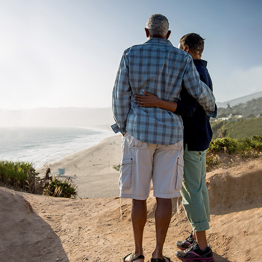 Older couple standing together overlooking a beach and the ocean during a sunny day