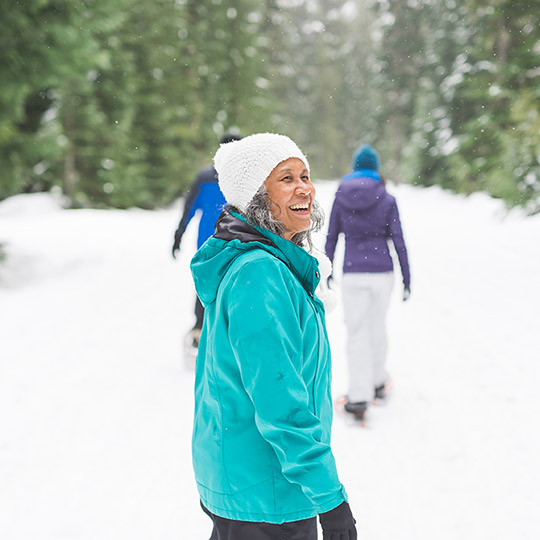 Older lady walking on a snow filled trail with two other women