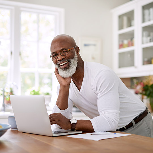 Older male leaning on a kitchen island in front of his laptop computer