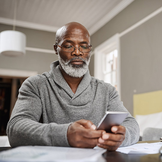 Older man wearing glasses sitting at his kitchen table and looking down at his mobile phone