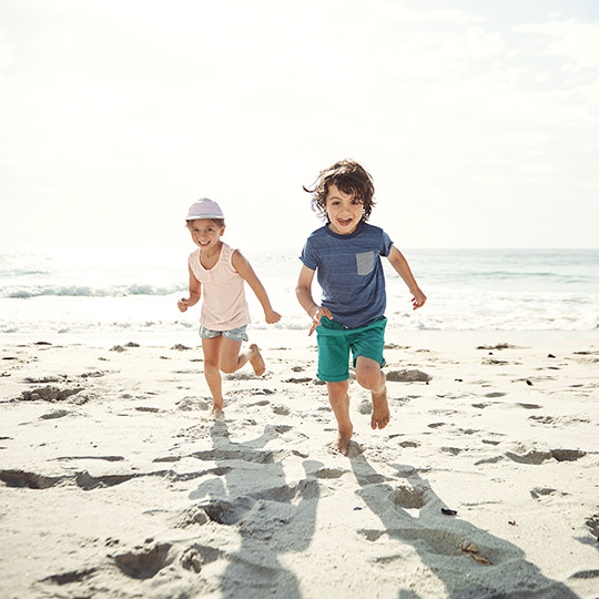 Two kids in shorts and t shirts running on a beach