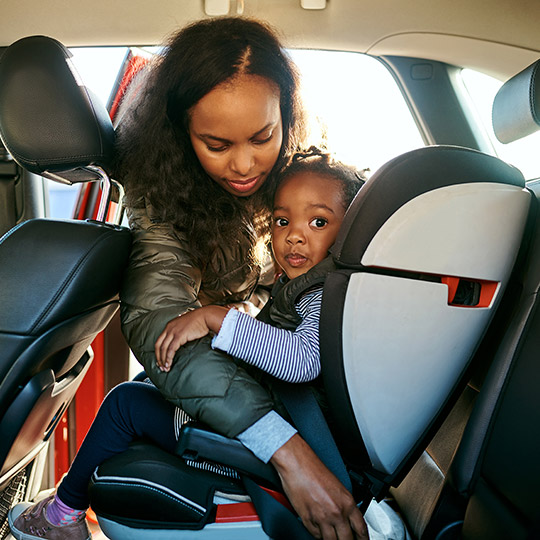 Woman buckling her youung daughter into a car seat in the back of a small car