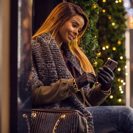 woman in winter coat sitting outside a store and looking at her mobile phone