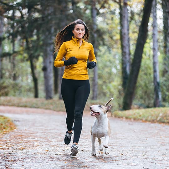 woman running on a paved path in the woods with her dog