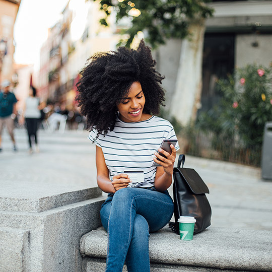 Woman sitting on concrete steps of a shopping center while holding a credit card and glancing at her mobile phone