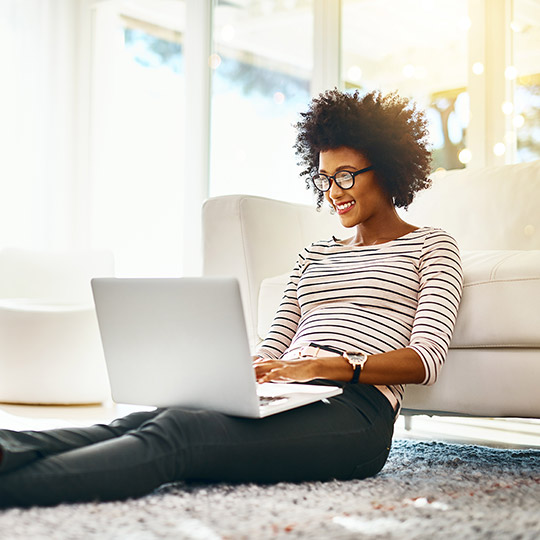 Woman sitting on her carpeted floor against the couch while working on her laptop
