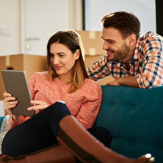 Younger couple looking at an iPad on a couch sorrounded by moving boxes in their new home