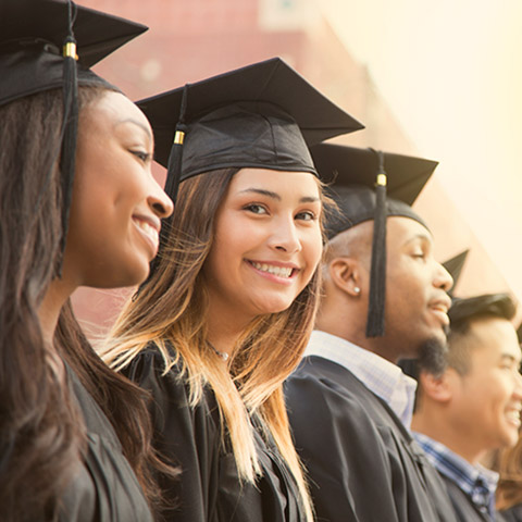 College graduates in cap and gown standing in a line while one of the girls smiles at the camera