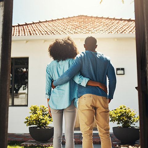 Couple standing arm in arm on the sidewalk in front of their home