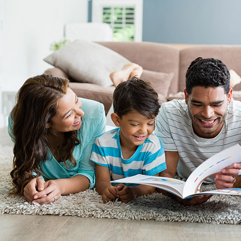 Family of four reading a book together on the living room carpet