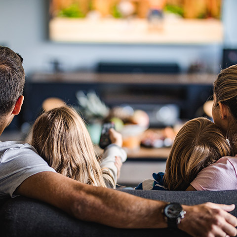 Family of two kids two parents sitting on a couch watching a movie together
