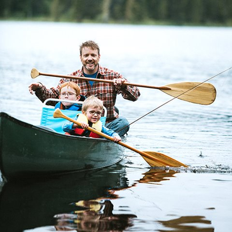 Father canoeing on a lake with his two young sons