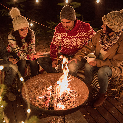 Four adults sitting around a fire roasting marshmallows in winter weather