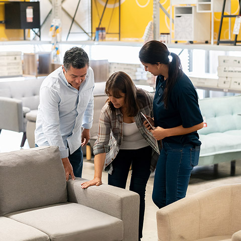 Man and woman in a furniture shopping for a couch while being helped by the female saleswoman
