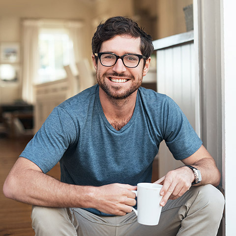 Man crouching down in his kitchen and smiling at the camera while holding a coffee mug
