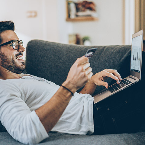 Man laying on his couch doing online shopping with his laptop and entering a credit card number