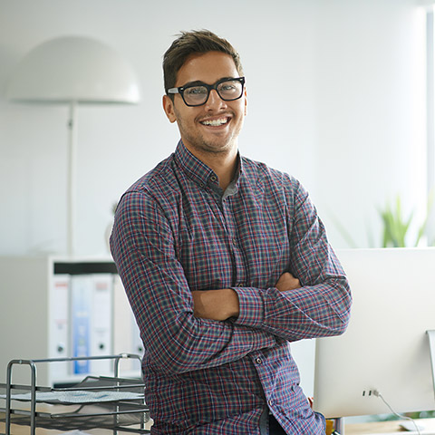 Man standing in front of his work desk smiling for the camera