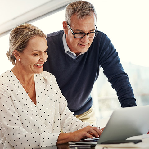 Older couple sitting at their kitchen counter looking at a laptop