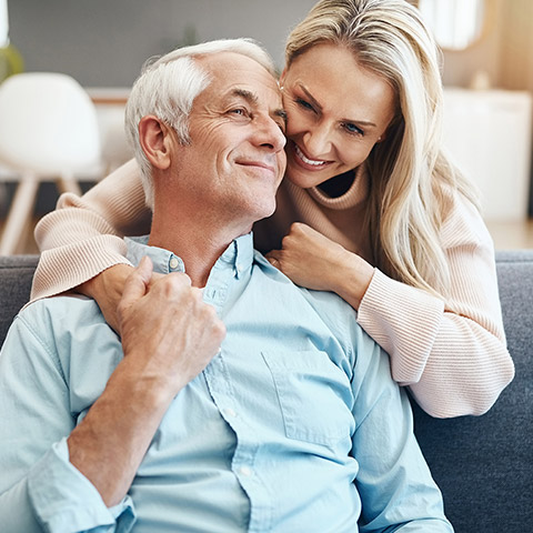 Older man sitting on a couch being hugged from behind by his wife_1