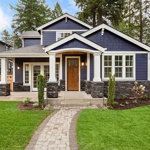 View from the front walkway of a two story home with blue siding and a red front door