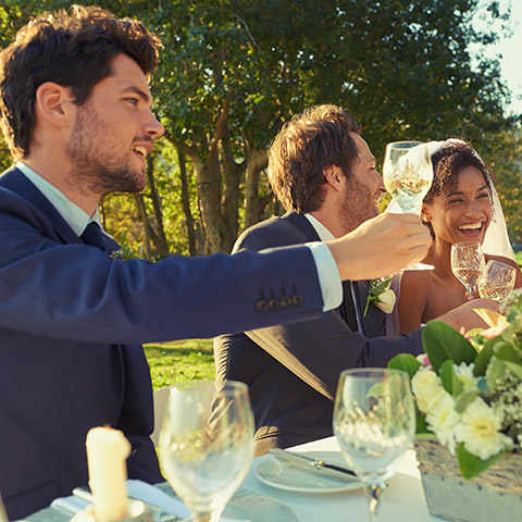 Wedding party sitting at table toasting glasses and laughing