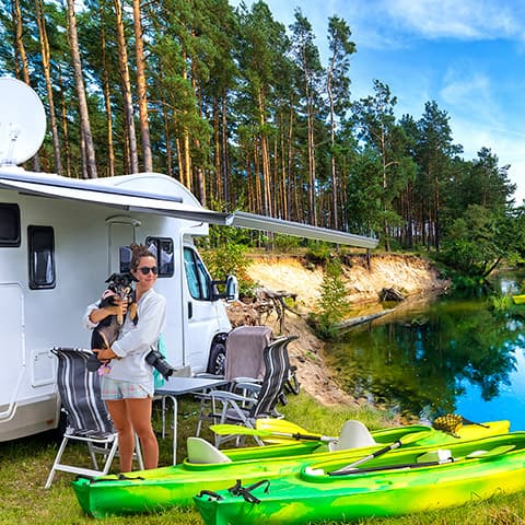 Woman holding a small dog and standing outside an RV which is parked by a river there are two kayaks near the water