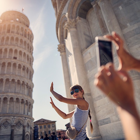 Woman posing lik she is holding up the Tower of Pisa while her friend takes a photo