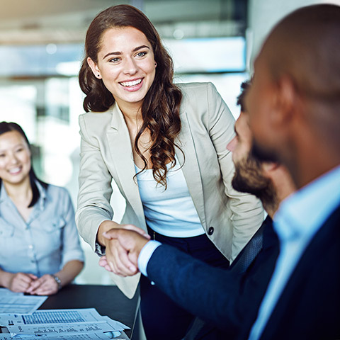 Woman shaking the hand of a client while others at the conference table look on