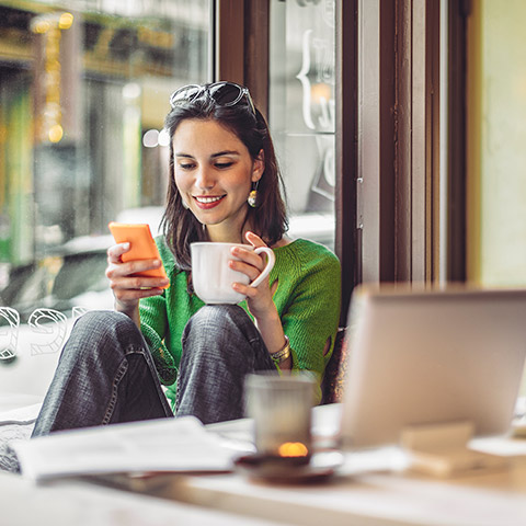 Woman sitting in a coffee shop looking at her mobile phone while holding a coffee mug