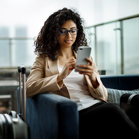 Woman sitting in an airport chair looking at her mobile phone