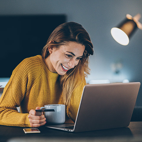Woman smiling while online shopping at laptop on a desk and hold a coffee mug and credit card
