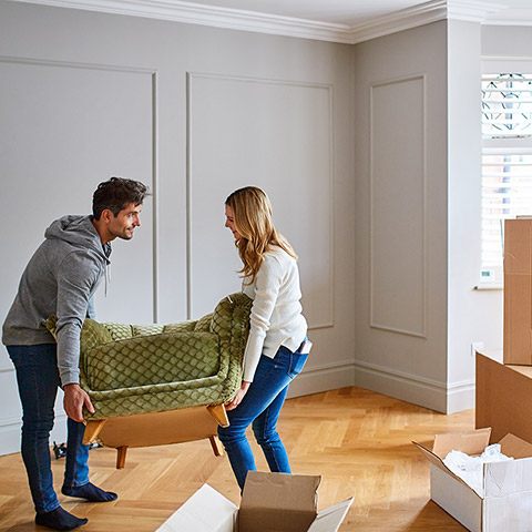 Young couple lifting a small couch in their newly purchased home sorrounded by moving boxes
