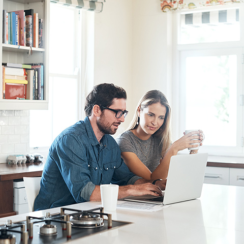 Young couple sitting at their kitchen island looking at a laptop