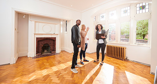 Realtor showing a couple a room in a home for sale room has a fireplace, hardwood floors, and a wall attached heating unit