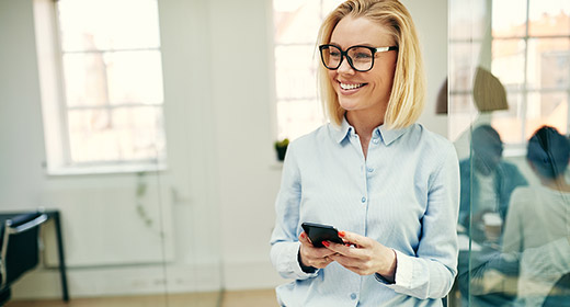 Woman in business casual clothes standing and holding her cell phone like she is preparing to make a call